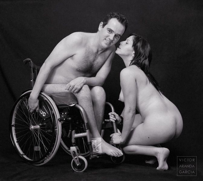 Un hombre con diversidad funcional desnudo en una silla de ruedas sonrie a la cámara mientras una mujer desnuda a sus pies se acerca a su cara para darle un beso