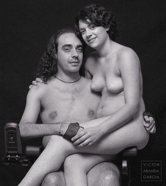 Fotografía de una pareja desnuda con la chica sentada junto al chico en una silla de ruedas