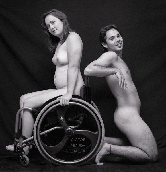 Fotografía de una mujer discapacitada desnuda erguida sobre una silla de ruedas con un chico desnudo arrodillado y apoyado de espaldas en la misma silla
