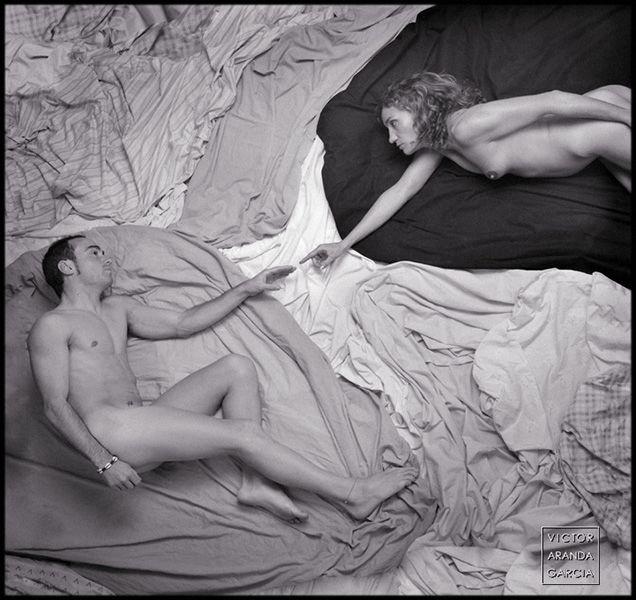 Fotografía en blanco y negro de dos personas desnudas que recuerda a la creación de Miguel Ángel en la capilla Sixtina