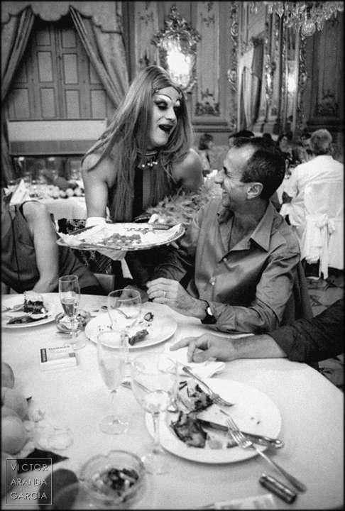 Fotografía en blanco y negro de un drag queen ofreciendo una bandeja de dulces a un chico