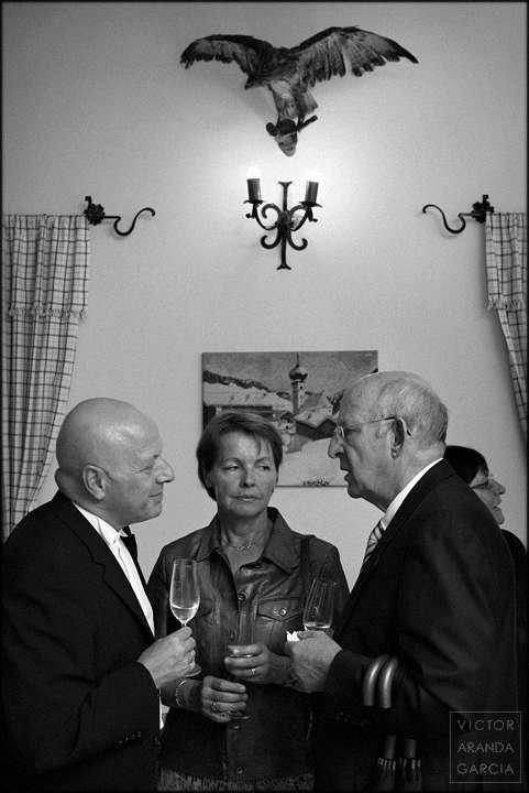 Fotografía en blanco y negro de tres personas hablando con copas en la mano bajo un ave disecada