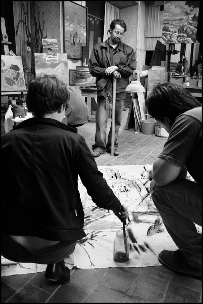 Fotografía en bllanco y negro de dos personas pintando un mural en el suelo mientras otra mira