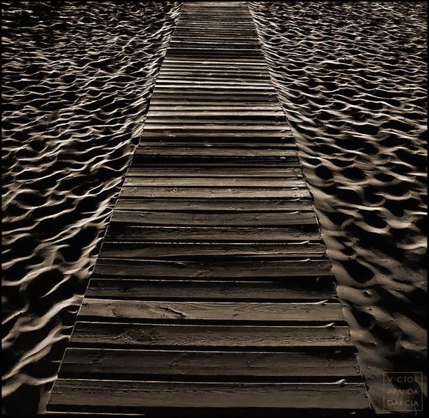 Fotografía nocturna de un camino de maderas entre la arena de la playa