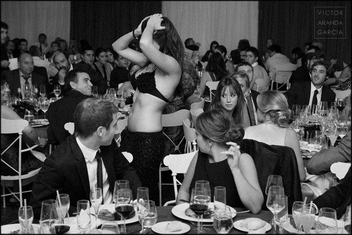 Retrato en blanco y negro de una mujer bailando entre las mesas de un evento