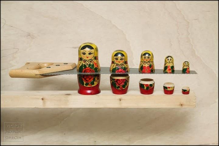 Fotografía artística de unas matrioskas cortadas por un serrucho sobre un fondo de madera