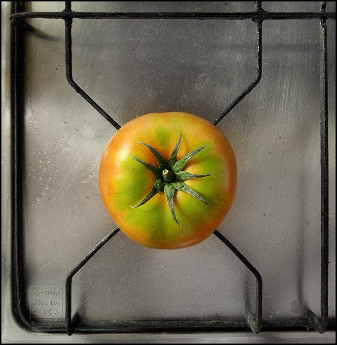 Fotografía artística de un tomate puesto sobre el fogón de una cocina