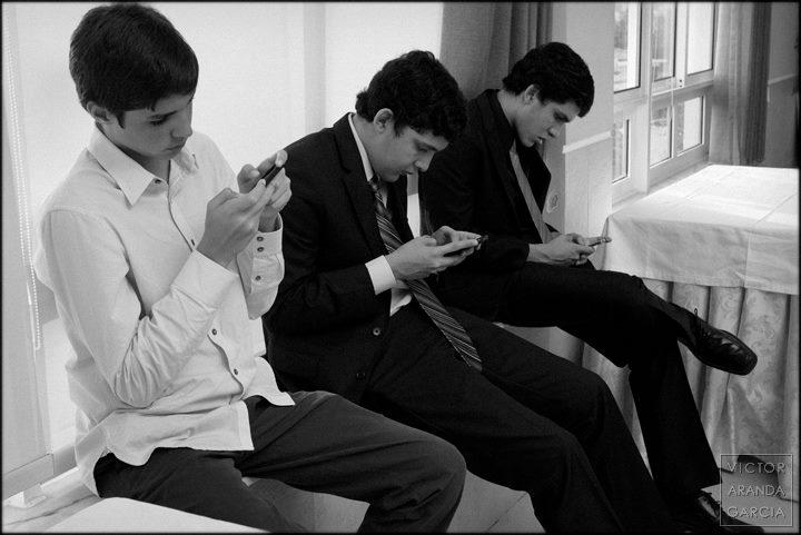 Fotografía de tres jóvenes mirando sus teléfonos