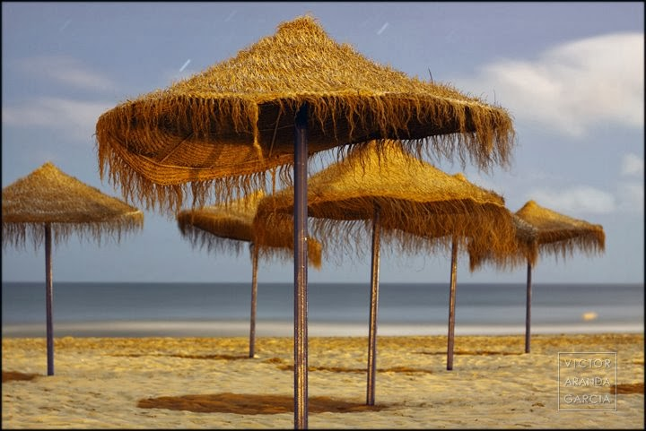 Fotografía nocturna de unas sombrillas de playa a la orilla del mar