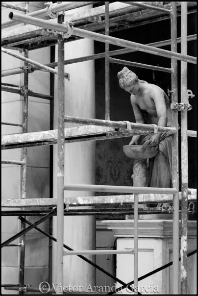 Fotografía de la escultura de una mujer vista entre los barrotes de un andamio