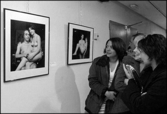 Varias mujeres miran una fotografía enmarcada en la pared en una exposición en Murcia