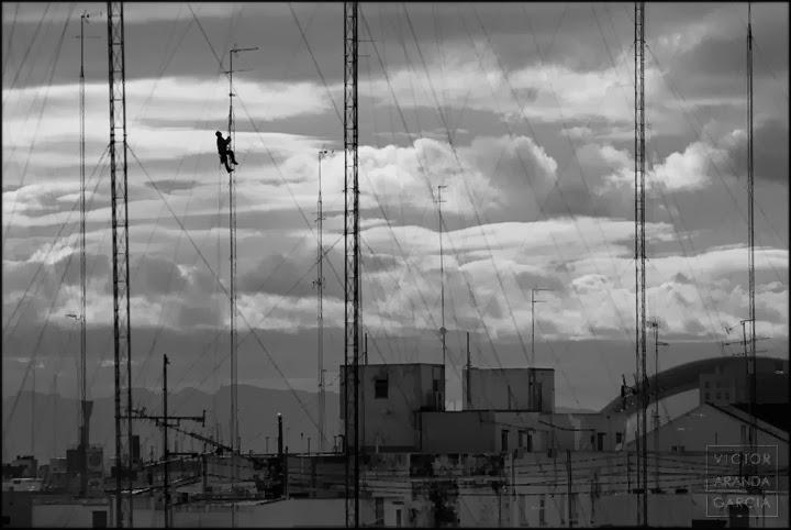 Fotografía de un hombre subido a una antena alta sobre las azoteas con un fondo de nubes