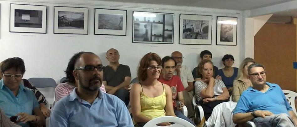 Fotografía del público asistente a la presentación de un libro con las fotos incluídas expuestas detrás