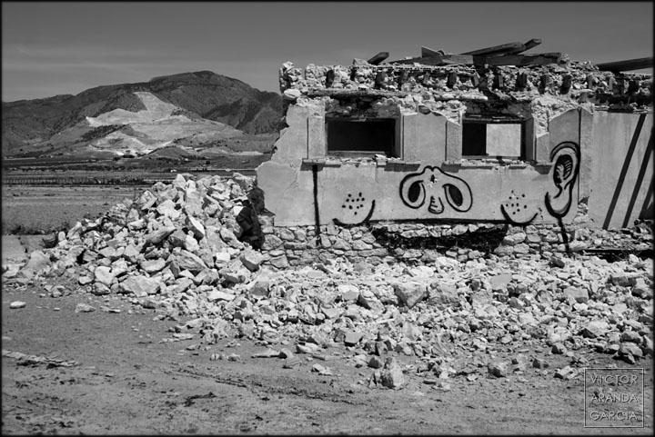 Fotografía de una casa en ruinas con una cara pintada en la fachada y una montaña con una cantera al fondo