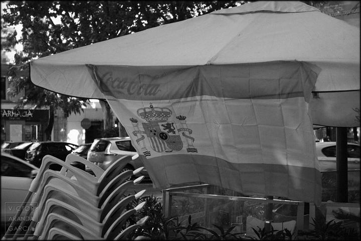 Fotografía en blanco y negro de una bandera de España colocada en una sombrilla con publicidad de Coca Cola