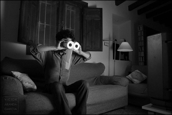 Fotografía de un hombre mirando la televisión sujetando dos rollos de papel higiénico delante de los ojos a modo de prismáticos