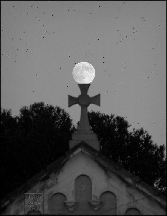 Fotografía de la luna llena vista justo sobre una cruz de piedra de la fachada del cementerio de Benimaclet