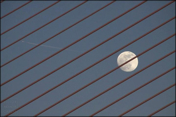 Fotografía de la luna llena vista a través de las barras de un puente en Valencia con un avión pasando y su estela