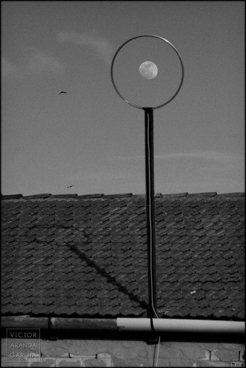 Fotografía de la luna vista a través de un artilugio circular sobre el tejado de una casa en Valencia