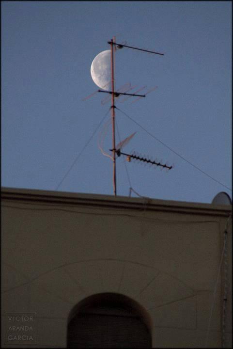 Fotografía de la luna en cuarto creciente vista justo al lado de una antena de televisión sobre una azotea