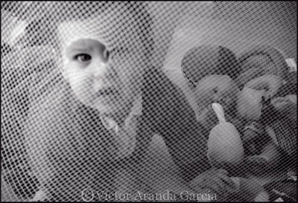Fotografía de un bebé mirando a través de un agujero que hay en su parquecito