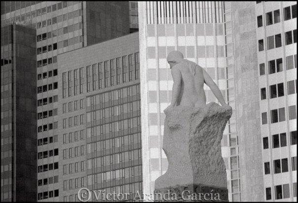 Fotografía en blanco y negro de la escultura de una mujer desnuda delante de varias fachadas de edificios modernos