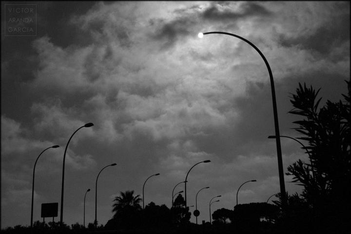 Fotografía en blanco y negro del sol visto justo en el extremo de una farola sin farol en un plano amplio en el que también hay otras farolas