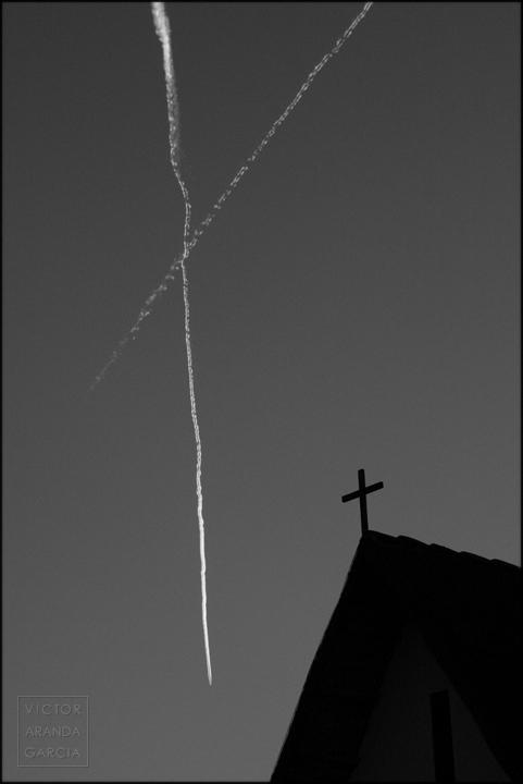 Fotografía de una casa tradicional de la huerta valenciana con una cruz sobre la fachada con las estelas de dos aviones dibujando otra cruz en el cielo