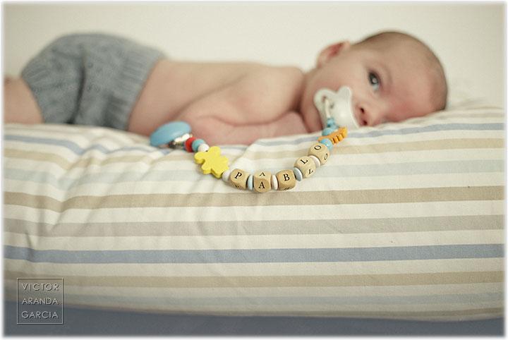 Fotografía de un recién nacido con una chupeta con un colgante con su nombre