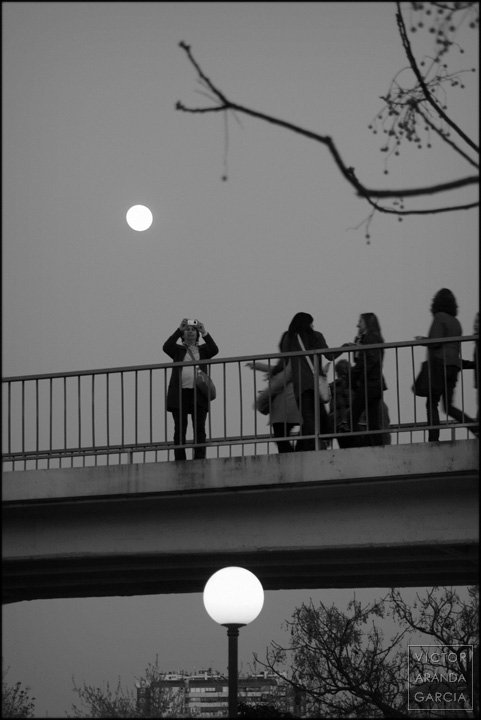 personas sobre un puente con una farola y la luna