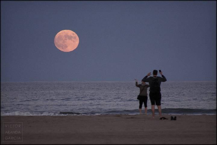 dos personas en la playa con la luna llena al fondo