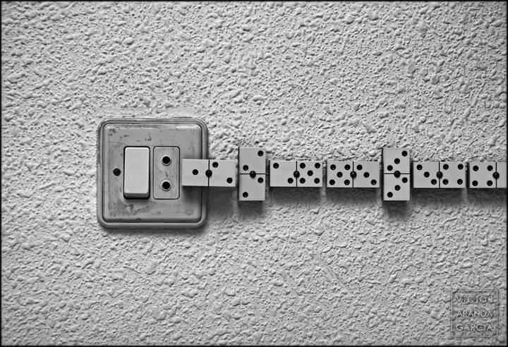 Fotografía de piezas de dominó junto a un enchufe