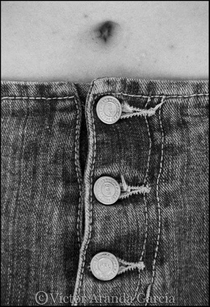 Fotografía de los botones de un pantalón bajo un ombligo