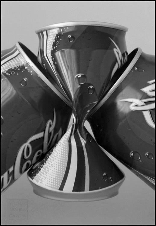 Fotografía en blanco y negro de tres latas de refresco