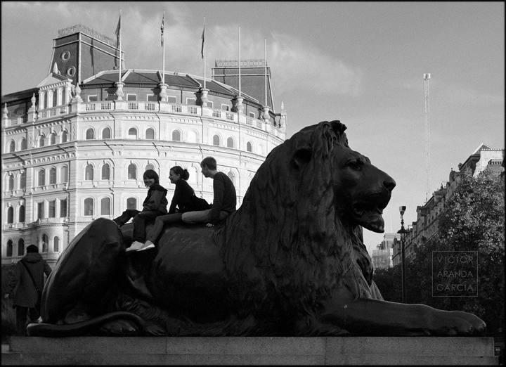 niños sobre escultura de león
