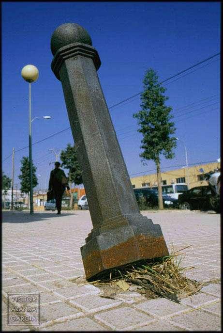 Fotografía de un poste metálico inclinado con unas hierbas creciendo debajo