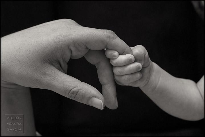 Fotografía de estudio de la mano de un recién nacido cogiendo la de su madre