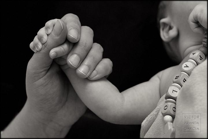 Fotografía en blanco y negro de un bebé dando la mano a su madre