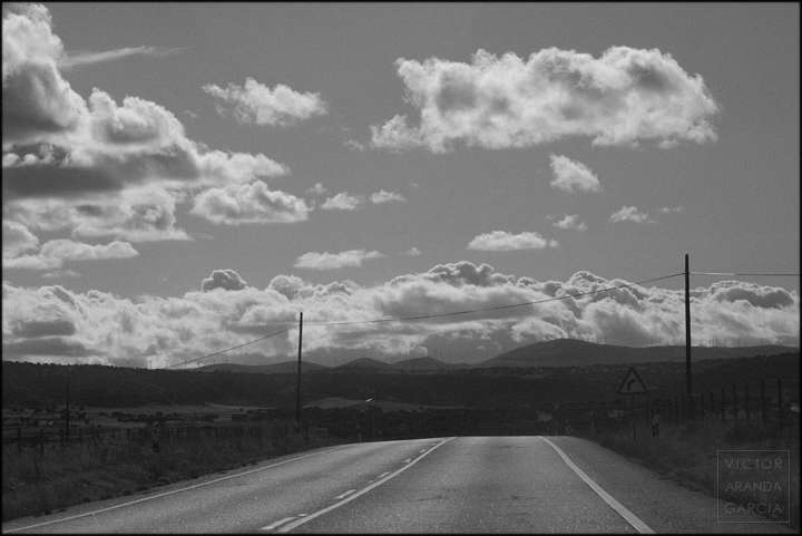 Fotografía en blanco y negro de una carretera con un paisaje de montes y nubes al fondo