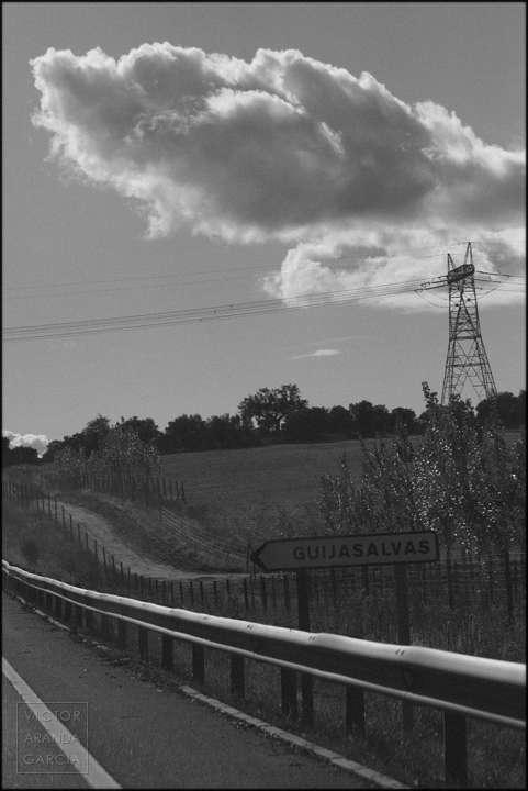 Fotografía del borde de una carretera con un paisaje rural de fondo