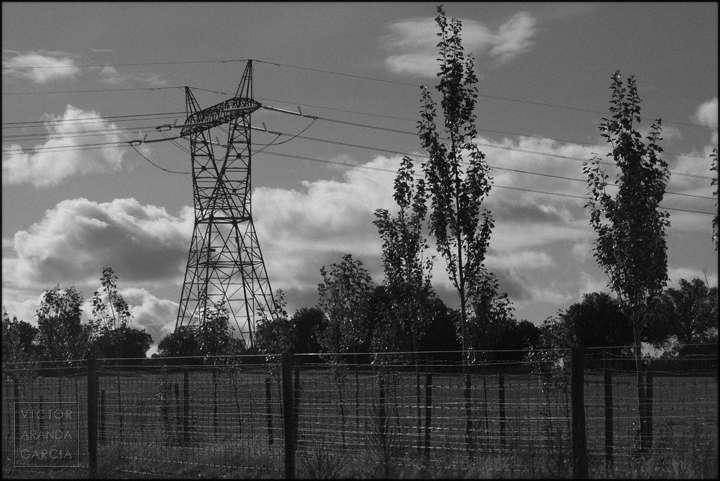 Fotografía en blanco y negro de una torre eléctrica en medio de un paisaje rural con vallas