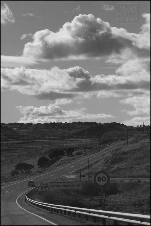 Fotografía en blanco y negro de una carretera que discurre entre montes y campos con nubes de fondo