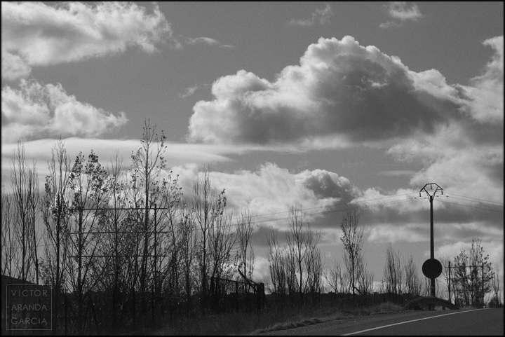 Fotografía en blanco y negro con naturaleza y nubes de fondo vistos desde una carretera