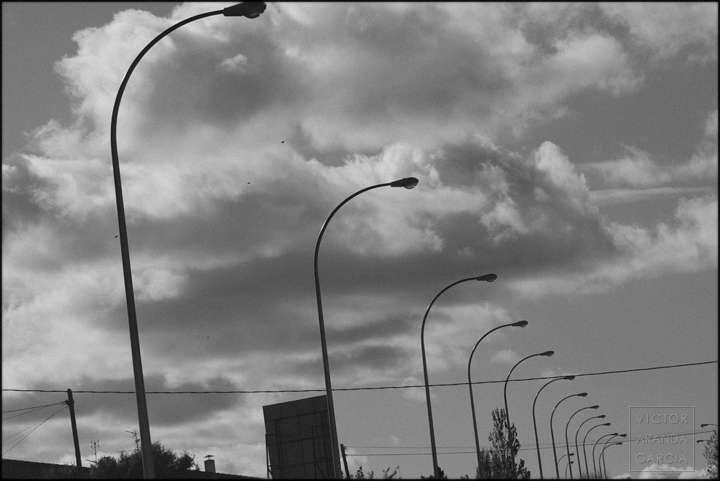 Fotografía en blanco y negro de un grupo de farolas con nubes de fondo