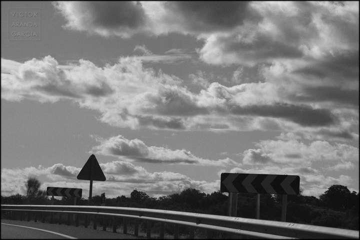 Fotografía en blanco y negro del límite de una carretera con varias señales de tráfico y nubes de fondo