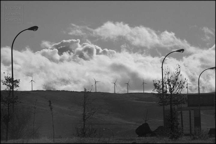 Fotografía en blanco y negro de varias farolas con molinos de energía eólica y nubes al fondo
