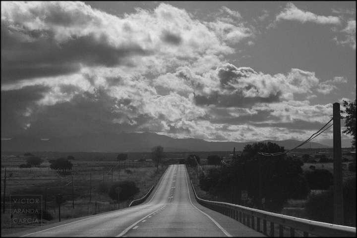 Paisaje en blanco y negro de una carretera con montañas y nubes al fondo