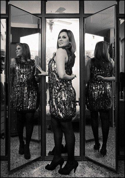 Retrato en blanco y negro de una mujer ante unos espejos