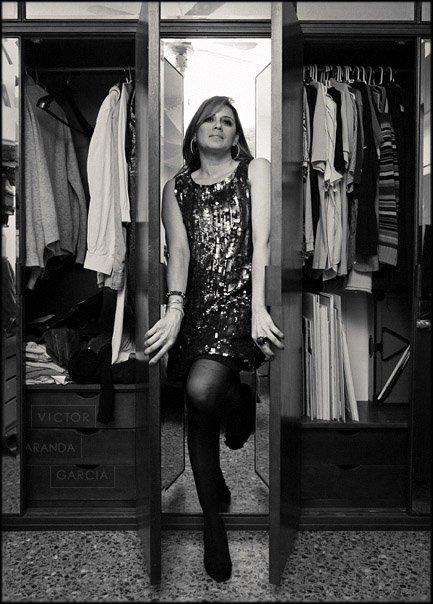 Fotografía en blanco y negro de una mujer entre dos armarios abiertos