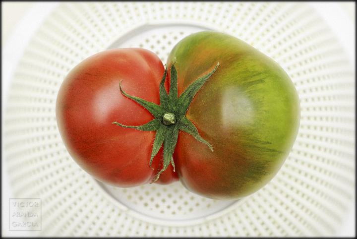 Fotografía de un tomate rojo y verde sobre un escurridor de verduras blanco
